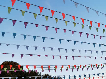 Multi-colored pennant, flags on the rope, festive decoration. Flags garland for fun festa party event, summer holiday farm feast celebration, carnival. Reklamní fotografie