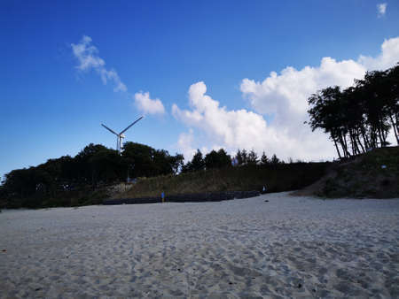 Beach. Baltic sea coast with sand, dunes and wind generator. Stock Photo