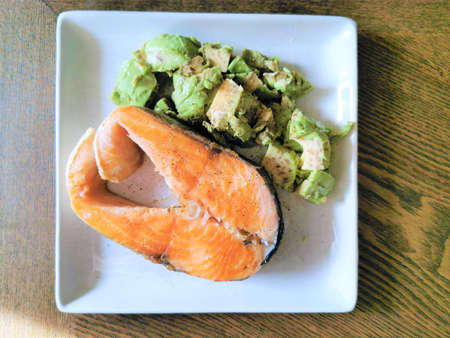 Salmon steak with avocado garnish. A high-fat, low-carb keto-diet dish.