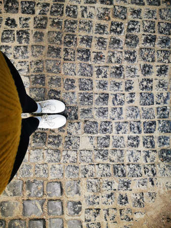 A woman stands on the old cobblestones. Feet in white sneakers, photo from top to bottom.