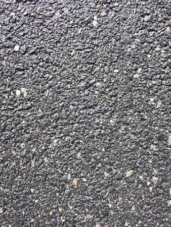 Black-gray empty surface of old asphalt or tarmac road. Noisy surface asphalt texture. Close-up photo