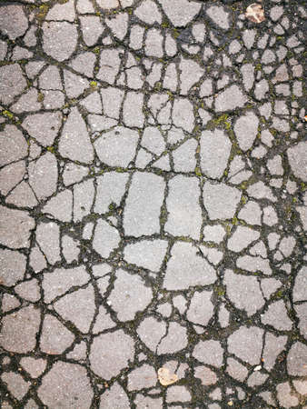 Old cracked asphalt road surface with many mosaic fragments. The old asphalt. Close-up photo.