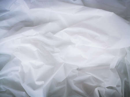 Wrinkled white fabric. Close-up photo. Abstract light, white background.