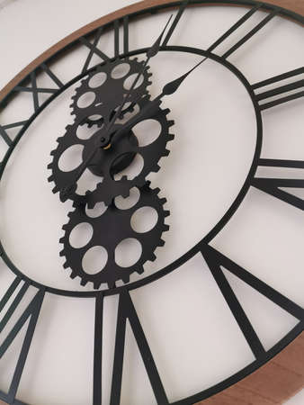Large wall clock with Roman numerals, decorative gears and wooden bezel. The loft-style. Close-up photography Stock Photo