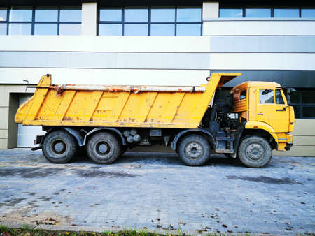 Big yellow truck. Construction equipment. The car for transportation of cargoes, loose substances with the reclining body. Freight transportation service. Drive engineering.