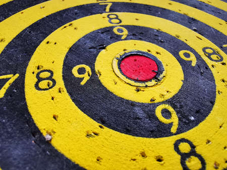 Target for throwing Darts. Black and yellow concentric circles with digital markings and dart marks. Goal achievement symbol. Abstract background. Empty space. Imagens