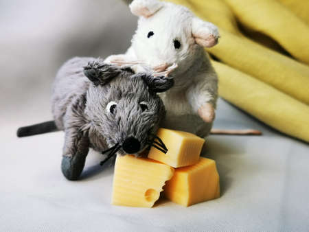 Two cute funny mouse with cheese, a symbol of the year 2020 on the astrological calendar. Photo of childrens toys close-up