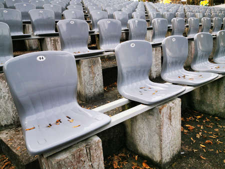 Rows of plastic gray seats in a public Park in front of the stage. Empty chairs covered with autumn leaves