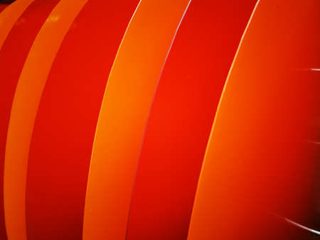 Bright wavy pattern with 3d effect. Photo of plastic panels. Dynamic style. Orange- Red background.Colorful wavy background. Geometric texture. Bright wavy background. Flyer backdrop.