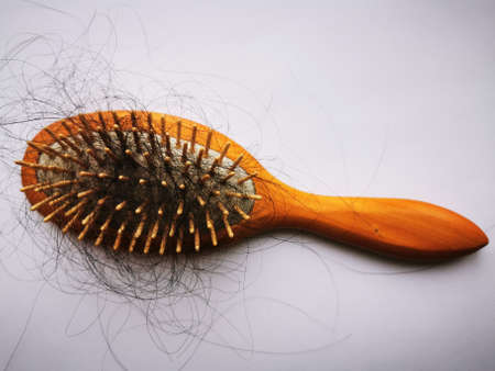 Lots of long black hair on the comb. Healthcare, medicine. Hair loss.