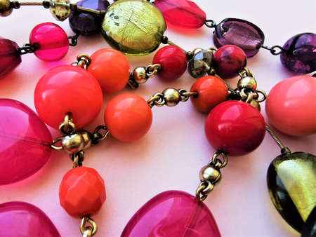 Jewelry, choker in boho style. Beautiful beads of different shades of pink, purple, coral flowers. Different shapes and facets. Close-up photo. Fashion art design.