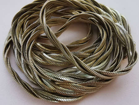 The chain is gold tone, the type of weaving snake. Close-up photo.