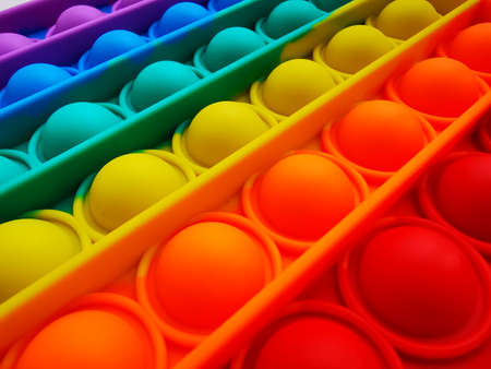 Anti-stress toy poppit. Push bubble toy. Rainbow colors. Close-up. Colored abstract background.