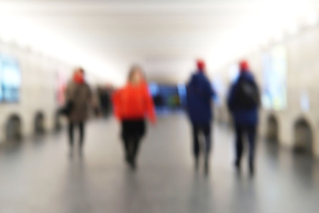 People walking in abstract subway. Blurred background.