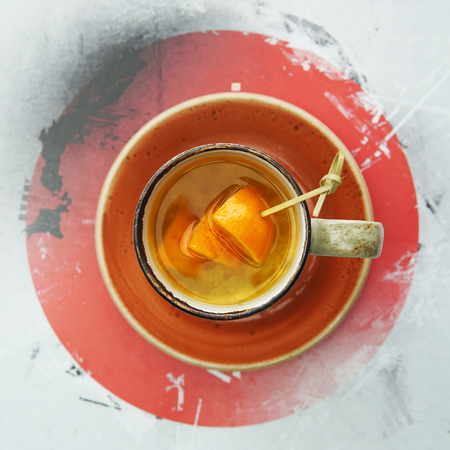 A cup of citrus tea with mango and orange slices on an orange saucer in a Japanese cafe. View from above. Imagens
