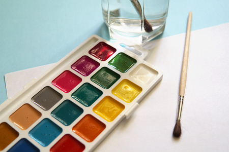 Workplace of an watercolor artist-painter. Blue background, new beautiful paints and brashes.