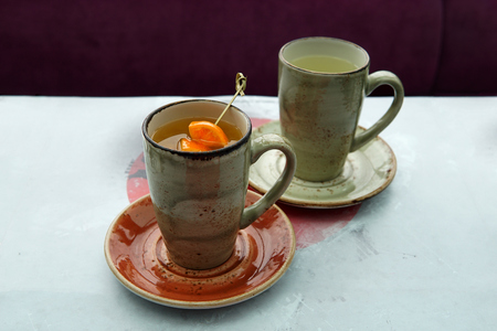 Two cups of tea: citrus tea with mango and orange slices and ginger hot tea in a Japanese cafe. Imagens