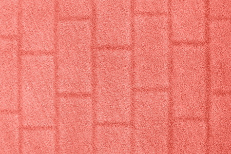 Coral color grass background with a brick wall texture. Color of the year 2019.