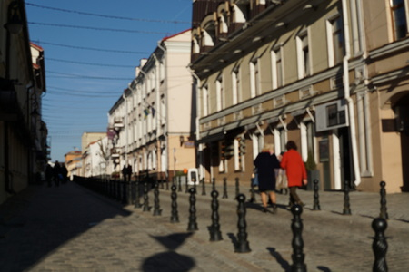 A group of people on the street and buildings on the background.