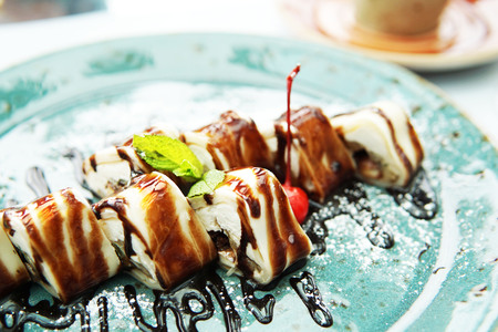 Dessert of pancakes in the form of rolls with cream cheese filling with mint on a blue plate, with syrup and chocolate topping.