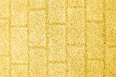 Yellow grass background with a brick wall texture. Color of summer 2019.