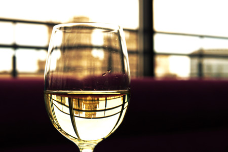 A glass of white wine, which reflects the beautiful building in the restaurant. Travel concept.