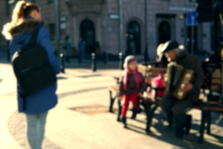 Blurred image of a little singing girl and an old man playing the accordion. Her mother look at them. The concept of the connection of generations.