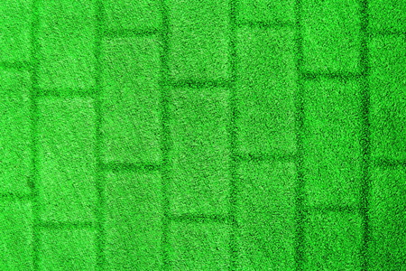 Green grass background with a brick wall texture. Imagens