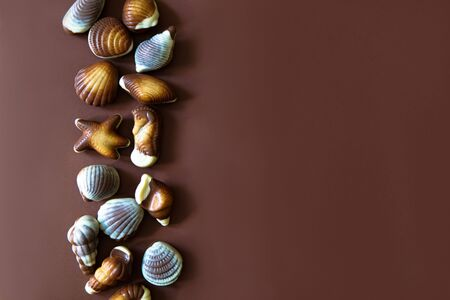 Assorted Chocolate pralines with sea concept on brown background. Copy space. Imagens
