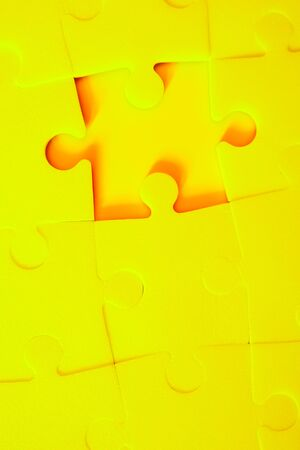 Multiple yellow puzzle pieces put together without one piece. View from above. Close up trendy monochrome image.