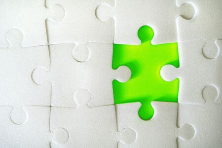 Multiple white puzzle pieces put together without one piece. View from above. Close up image. Imagens
