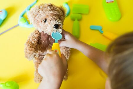 Child hands curing a bear. Kid toys medical equipment tool: stethoscope, thermometer, spoon, phone on yellow background Imagens