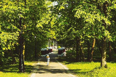 A little girl in the park rides a scooter on the road among thick bright green trees.