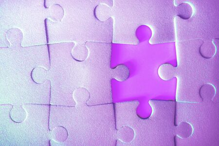 Multiple purple puzzle pieces put together without one piece. View from above. Close up trendy neon monochrome image.