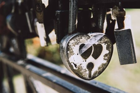 Many love padlocks locked on iron railing on a blurred background. Tourists place. Love sign and romance concept. Imagens
