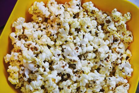 Yellow plate with popcorn. Close up, top view. Imagens