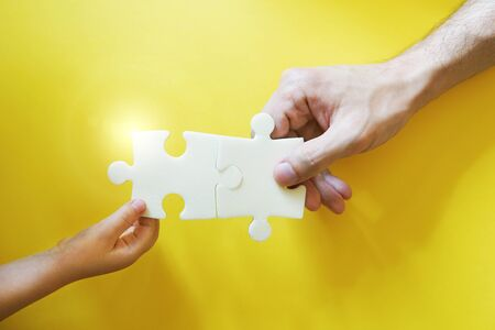Child and father hands taking pieces of puzzle. Happy and friendly family concept. Bright yellow backrgound.
