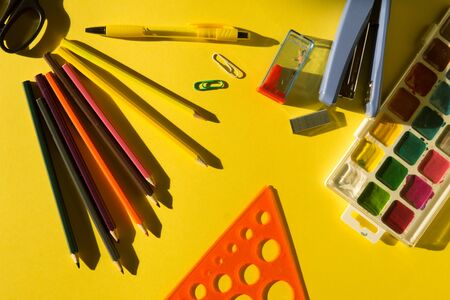 School supplies on a yellow background in bright sun lught. Back to school concept. 写真素材