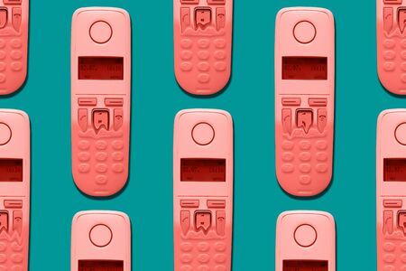 Pattern image of coral color DECT phones turning into a toy phones on blue background. The concept of technology obsolescence.