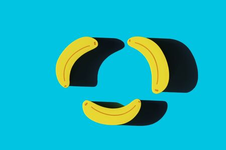 Pattern of three toy bananas isolated on blue background.