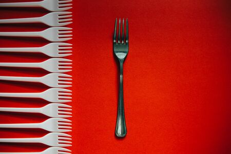 A lot of plastic forks vs one metal on a red background. The concept of environmental problems, environmental pollution by plastic waste. Top view. 版權商用圖片 - 129923177