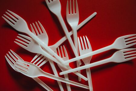 A lot of white plastic forks on a red background. The concept of environmental problems, environmental pollution by plastic waste. Top view, close up. 版權商用圖片 - 129923179