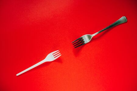 A plastic fork vs metal one on a red background. The concept of environmental problems, environmental pollution by plastic waste. Top view. 版權商用圖片
