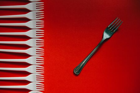 A lot of plastic forks vs a metal one on a red background. The concept of environmental problems, environmental pollution by plastic waste. Top view.