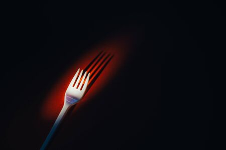 A plastic fork on a red background in dramatic light. The concept of environmental problems, environmental pollution by plastic waste. Top view. 版權商用圖片 - 129923185