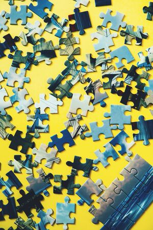 A lot of blue puzzle pieces on a yellow background. Vertical. Top view, flat lay.