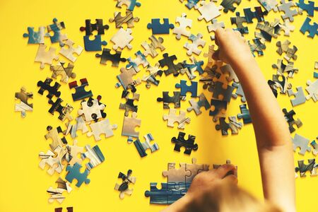 Hands of a child playing a puzzle. Yellow background, top view, flat lay.