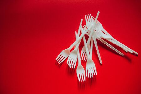 A lot of plastic forks on a red background. The concept of environmental problems, environmental pollution by plastic waste. Top view, close up.