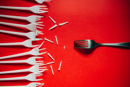 A lot of broken plastic forks vs a metal one on red background. The concept of environmental problems, environmental pollution by plastic waste. 版權商用圖片
