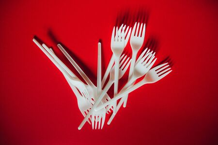 A lot of plastic forks on a red background. The concept of environmental problems, environmental pollution by plastic waste. Top view, close up. 版權商用圖片 - 129923154